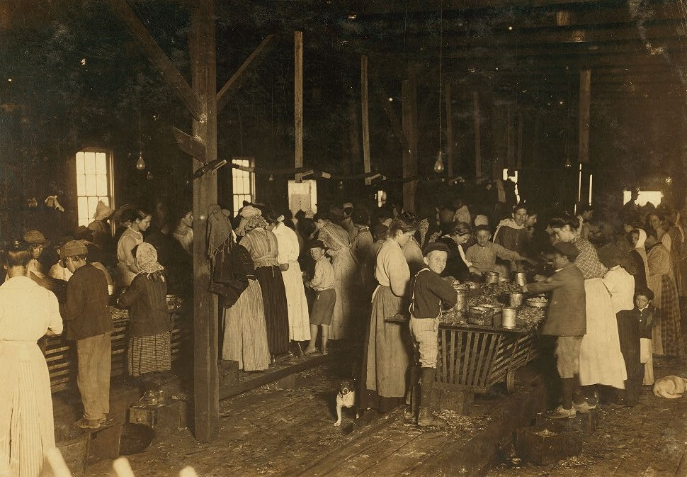 "View of the Gorenflo Canning Co., Biloxi, Miss. Taken at 7 A.M. Many tiny workers here, some of whom began to arrive as early as 5 O'clock, and [sic] hour before they were allowed to begin work, and long before daylight on a damp, foggy day. The whistle had blown and they came and stood around merely to hold their places. When the ""catch"" has been good they begin work early, but today it was not good so they were waiting for daylight. In this group I ascertained the ages of a few, as follows, 1 child of 6 yeards, 1 of 7, 2 of 8, 1 of 10, and there were many others. See report also. Location: Biloxi, Mississippi. March 1911 (Photograph by Lewis Hines -documenting child Labor)"