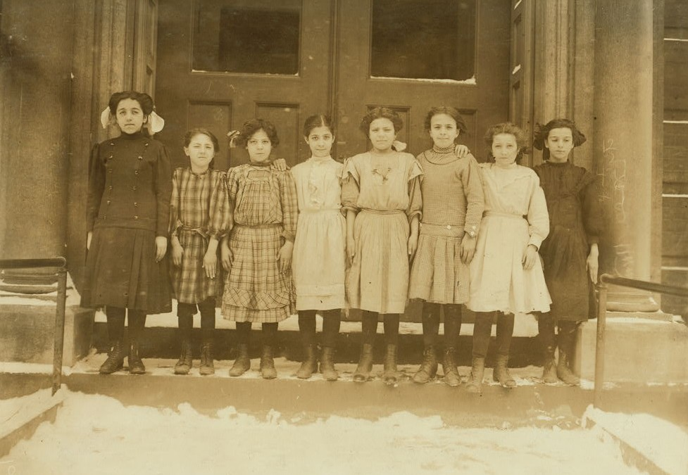 Group of Cannery Workers, School #1, Buffalo, N.Y. (from left to right): 1) Rose Paralto, 12 years old last summer. Helped mother on strawberries, Canning Factory, Simcoe, Canada. Entered school , January 3d, 1910. Last year, school work excellent, this year not good. 2) Josephine Pellina, 10 years old last summer. Strings beans in sheds of Forestville[sic?], Cannery. Came to school in September. 3) Christian Cengo, 10 years old last summer. Worked stringing beans in sheds Forrestville Cannery sometimes until 8 or 9 P.M. 4) Anna Gengo, 10 years old last summer. Sheds of Forrestville Cannnery. 5) Metea Spana, 13 years old last summer. Worked on peas and beans in the sheds of Eden Center Canning Factory. 6) Josephine Leone, 12 years old last summer. Helped in the sheds at Barker Cannery. 7) Frances Imperllario, 11 years old last summer. Worked on berries Cherry Creek Factory. 8) Mary Lefesso, 12 years old last summer. Worked at Barker Canning Factory. Entered school October 22d. Location: Buffalo, New York (State) Photo by Lewis Hines March 1910