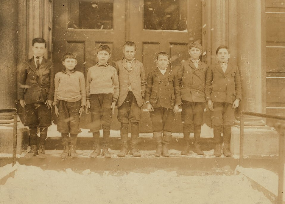 Group of boys from canning factories. School #1, Buffalo, N.Y. (from left to right): 1) Frank Lefasso, 13 years old last summer. Worked in canning factory at Barker. 2) Anthony Traeisi[?], 10 years old last summer. Worked on beans South Dayton, Cannery. 3) James Schillacer, 12 years old last summer. Earned 50 cents a day putting cans in holes in factory St. Catherines, Canada. 4) Peter Delsalvo, 13 years old last summer. Worked in the factory at Brant, N.Y. 5) Anthony Baraone, 11 years old last summer. Worked on apples, beans, tomatoes, in factory at Wilson, N.Y. 6) Thoma Laessi, 12 years old last summer. Worked on beans in sheds at Hamburg, N.Y. 7-9 A.M.; 3-5 P.M. 7) Joseph Lanca, 12 years old last summer. Strings beans in sheds. (All these boys worked on tomatoes.) Location: Buffalo, New York (State) photo by Lewis Hines March 1910