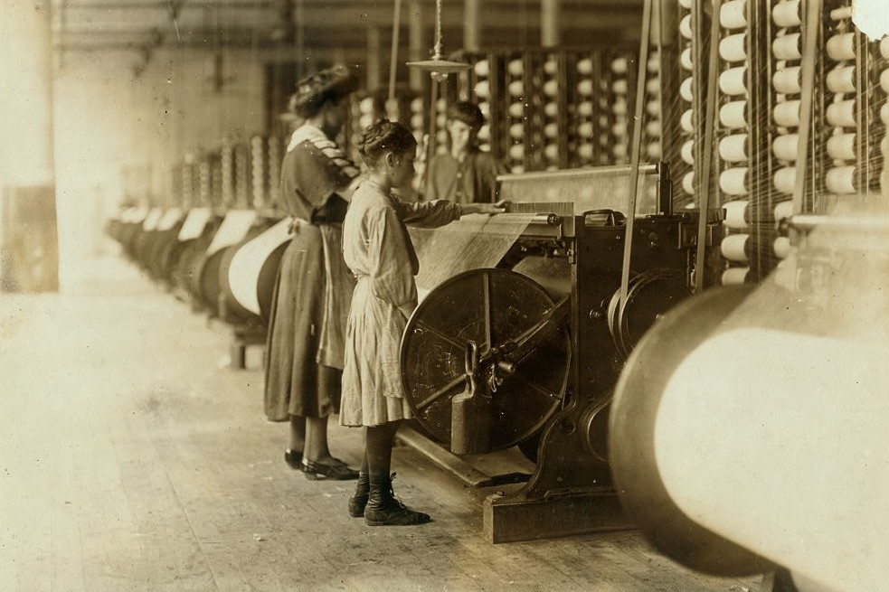 "Girls running warping machines in Loray mill, Gastonia, N.C. Many boys and girls much younger. Boss carefully avoided them, and when I tried to get a photo which would include a mite of a boy working at a machine, he was quickly swept out of range. ""He isn't working here, just came in to help a little."" Location: Gastonia, North Carolina. Nov. 1908"
