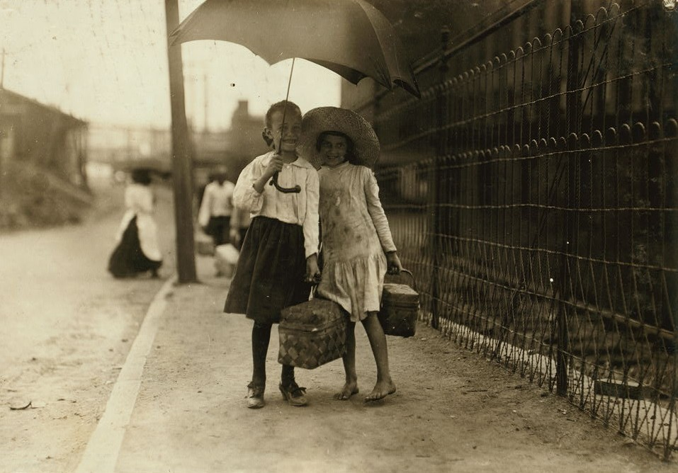 A couple of dinner-toters at Riverside Cotton Mills, Danville, Va. Myriads of these little ones carry dinners to the mill workers. The Supt. of Schools and teachers in Danville said that many children toted dinners and did nothing else not even attending school. Location: Danville, Virginia. ca. 1910 photo by Lewis Hines