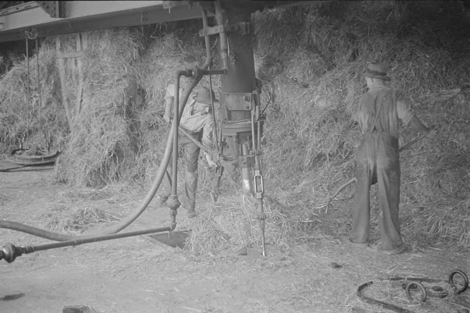 baled straw two men working