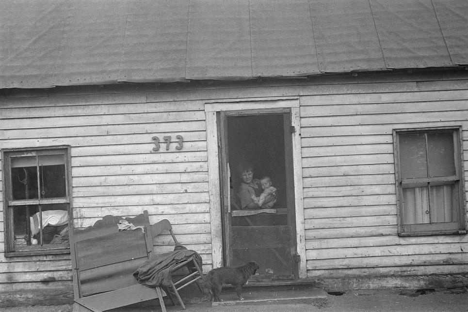 hooverville boy with baby in door