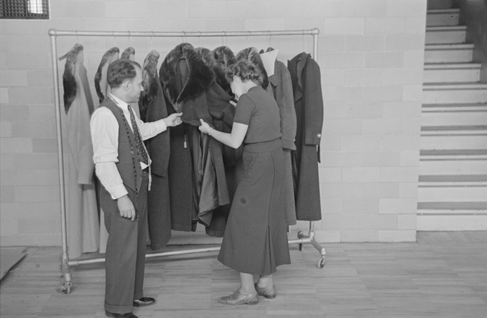 Sam Schultz shows a model coat to a perspective customer at the cooperative garment factory, Jersey Homesteads nov. 1936 russ