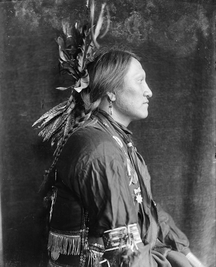Charging Thunder, Sioux Indian turned right, wearing a feathered headdress.