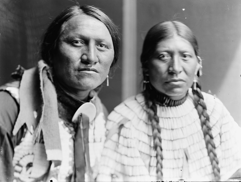 Charging Thunder and wife, probably members of Buffalo Bill's Wild West Show, head-and-shoulders portrait, facing front