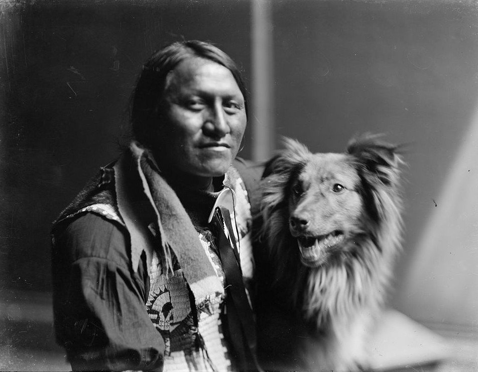Charging Thunder with dog, probably members of Buffalo Bill's Wild West Show, head-and-shoulders portrait, facing front