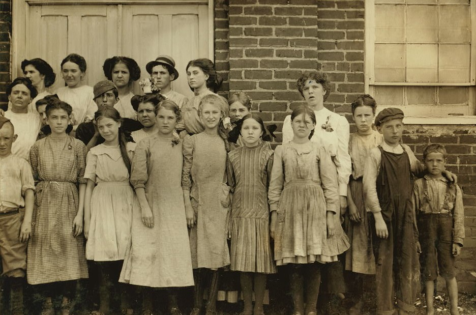 Comparison of Ages. Some of the youngest workers in Roanoke Cotton Mills. On right-hand end is seven year old Frank, a helper. Next to him is twelve year old Ronald, a doffer.