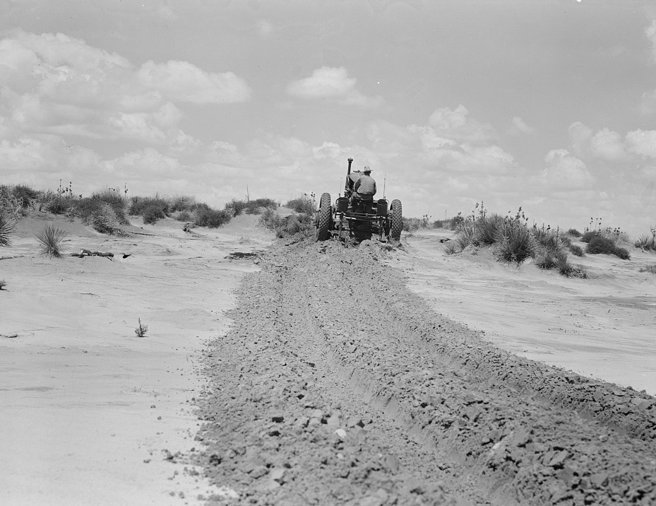 Leveling hummocks in dust bowl, thirty miles north of Dalhart, Texas. Farmer