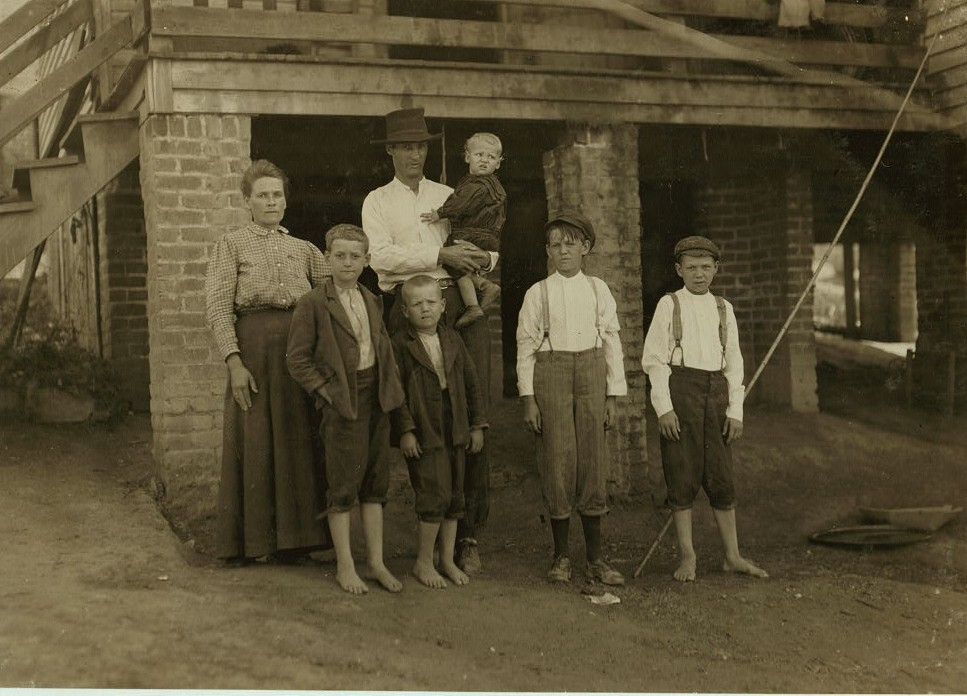 S.D. Ison and family. Father works some. Both boys on right of photo have been in Washington Cotton Mills, Fries, Va., for four years. When I asked the smallest worker how old he was, he said,