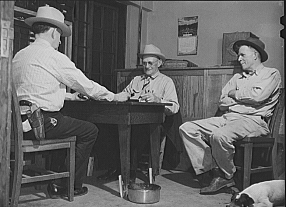 San Augustine, Texas. Lud Behnholder, filling station operator, watching night marshall Jeff Davis and the Justice of the Peace H.L. Armstrong in a domino game John Vachon April 1943