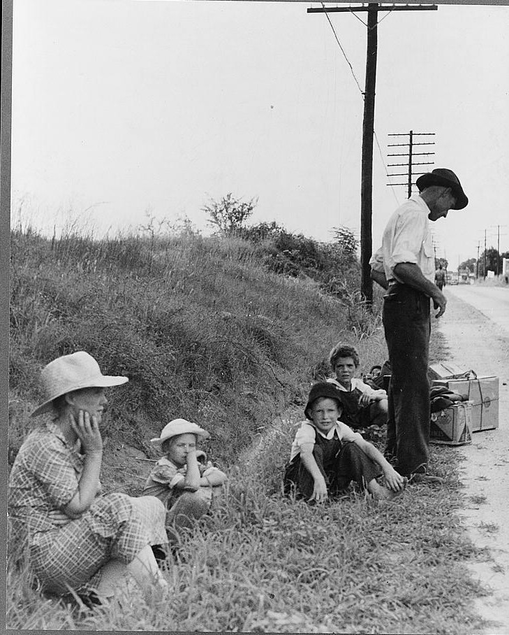 A hitchhiking family waiting along the highway