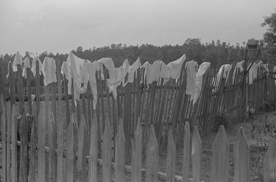 Hanging clothes on fence to dry, Greene County, Georgia