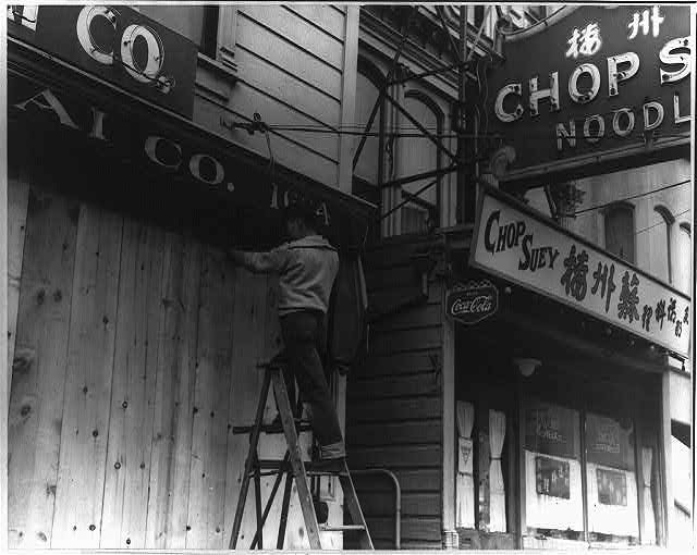Japanese-American boarding up store front before evacuation, San Francisco