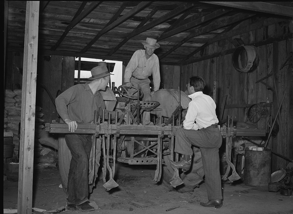 Farmer inspecting farm equipment
