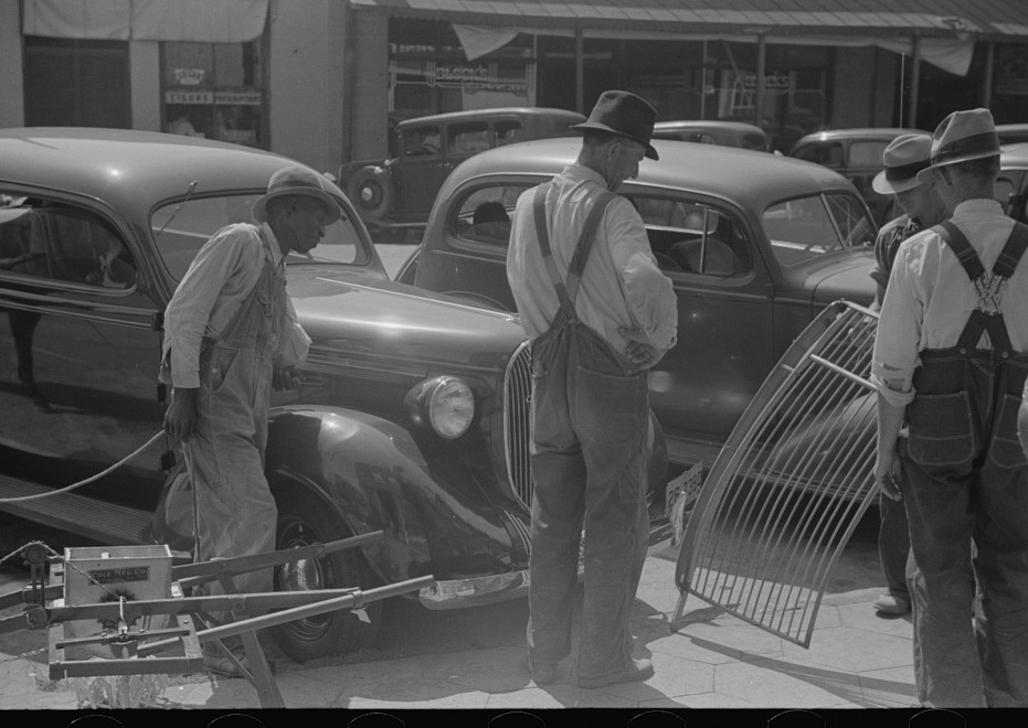 Hardware and farmers' supply store, Greensboro, Georgia. Farmers examining implement on sidewalk in front of store