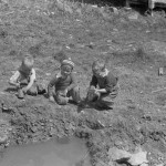 Children playing in street gutter in front of their home. Company coal town, Kempton, West Virginia
