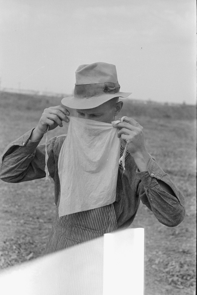 Farmer adjusting mask to avoid dust in haying operations. Lake Dick Project, Arkansas by Russell Lee Oct 1938