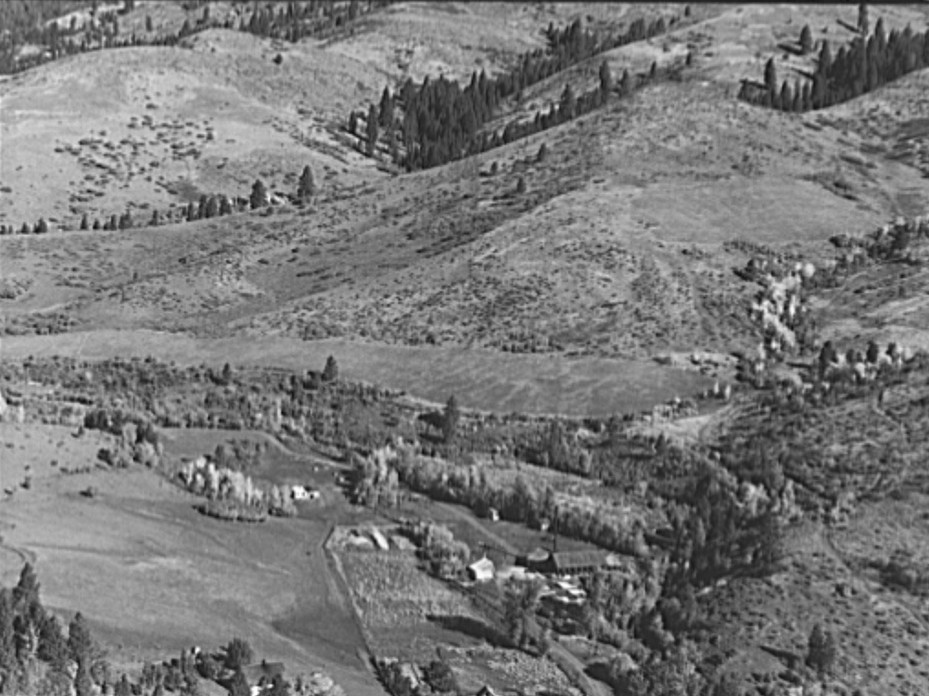 Looking down on Ola self-help co-op mill showing the upper end of Squaw Creek Valley, the creek lined with trees, the new dry shed near the mill, homes of