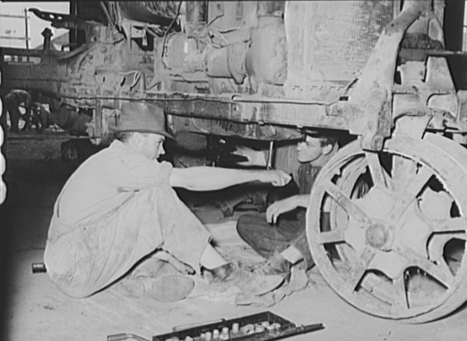 Member of cooperative association working on tractor. Lake Dick Project, Arkansas