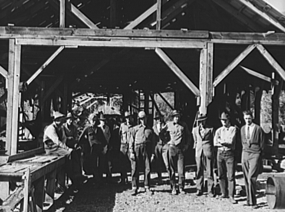 Men working in mill. Ola self-help sawmill co-op. Gem County, Idaho. Man in rear center in black hat is FSA (Farm Security Administration) county supervisor.