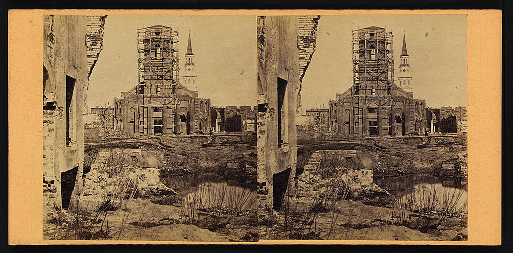 Photograph shows scaffolding on the Circular Church, steeple of St. Philip's Church, and ruins of Secession Hall in Charleston, South Carolina.