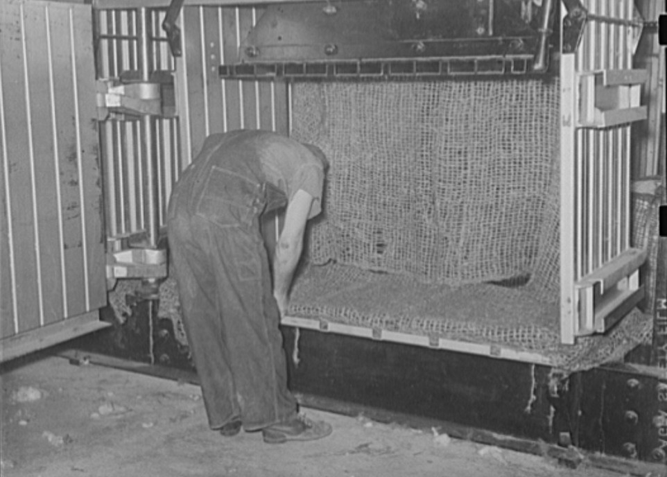 Placing burlap wrappings in compressor. Lake Dick Project, Arkansas