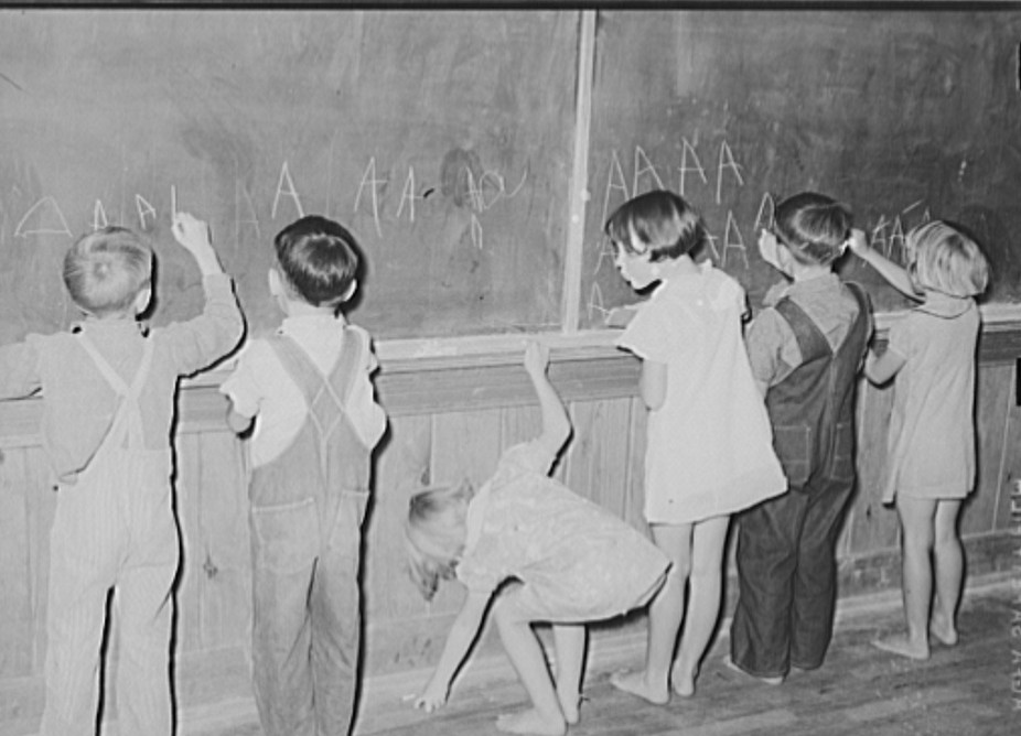 Students practicing letters on the blackboard