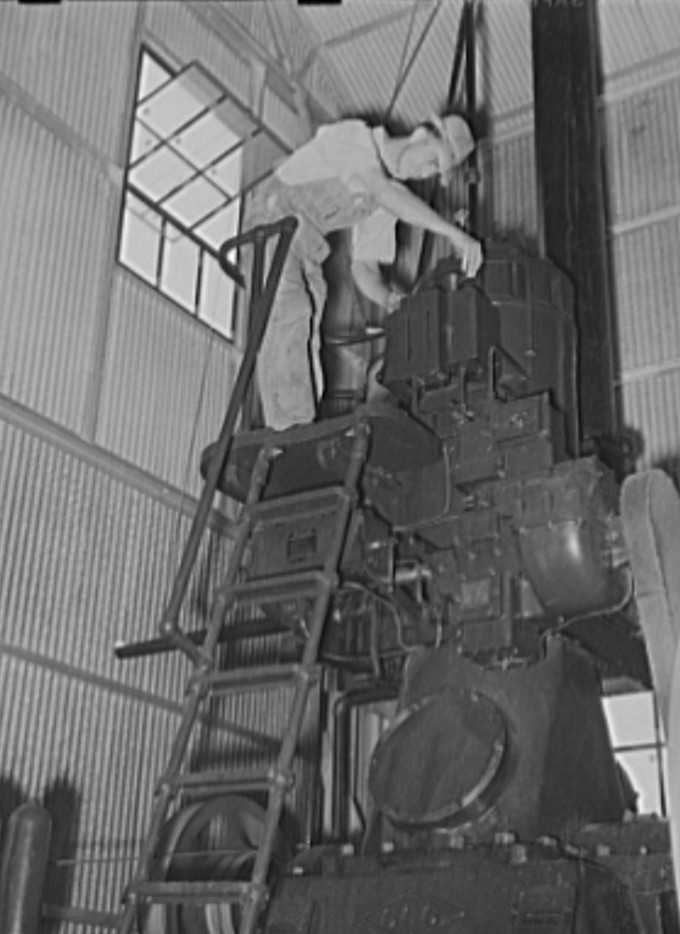 Working on diesel engine in power plant of cotton gin. Lake Dick Project, Arkansas