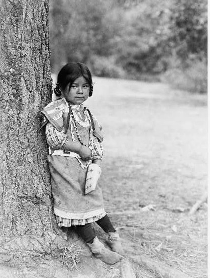 Innocence, an Umatilla girl, full-length portrait, standing by tree, facing slightly right by Edward S. Curtis ca. 1903
