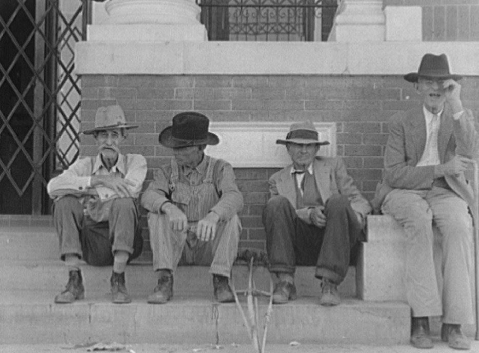 On the steps of the bank in the town square. Memphis, Texas by Dorothea Lange June 1937