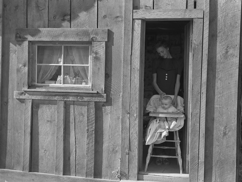Wife and baby of president of Ola self-help sawmill co-op in doorway of their home.