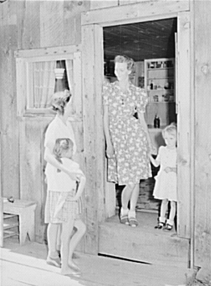 Wife of a member talks with her visiting neighbor who is also a member of the cooperative. The mother and child standing in the doorway are the same as in photograph