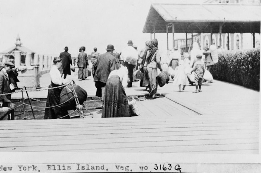 Dock with immigrants in foreground. between 1909-1932