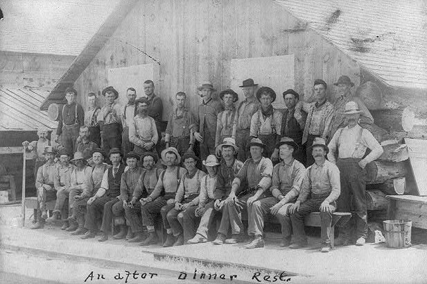 Group of 31 lumberjacks posed outside camp bldg