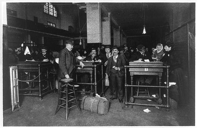 Immigration officers examining documents and immigrants at Ellis Island Immigration Station for final discharge ca. 1902