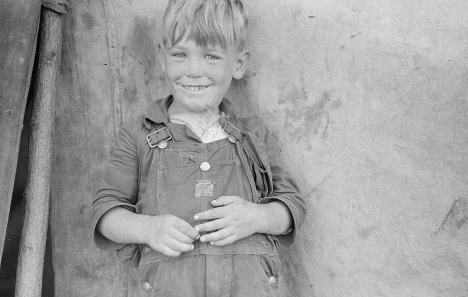 Migrant child eating in front of tent home, Berrien County, Michigan 1940