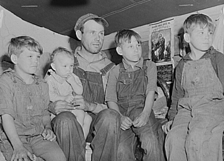 Migrant father and sons living in back of truck in fruit pickers camp. Berrien County, Michigan. The two older boys work with their father picking cherries 1940