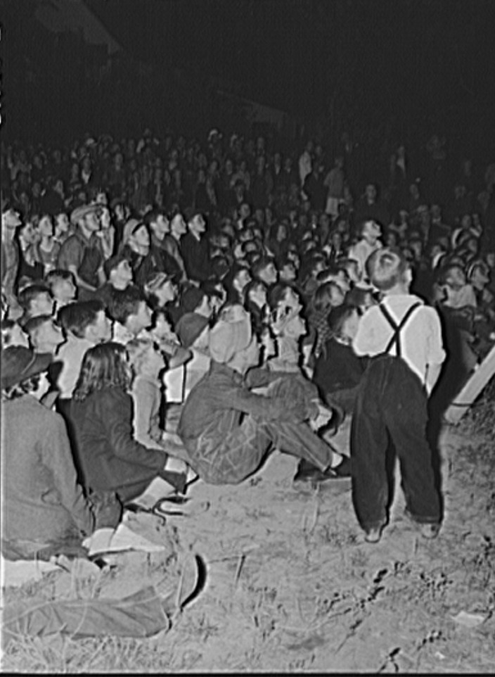 Migrant fruit workers come to town on Saturday night for a free open air movie sponsored by the local merchants who remain open for business. Millburg, Michigan 1940