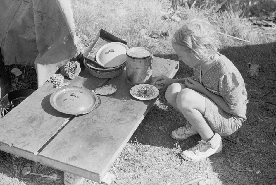 Migrant girl eating in front of tent home, Berrien County, Michigan 1940