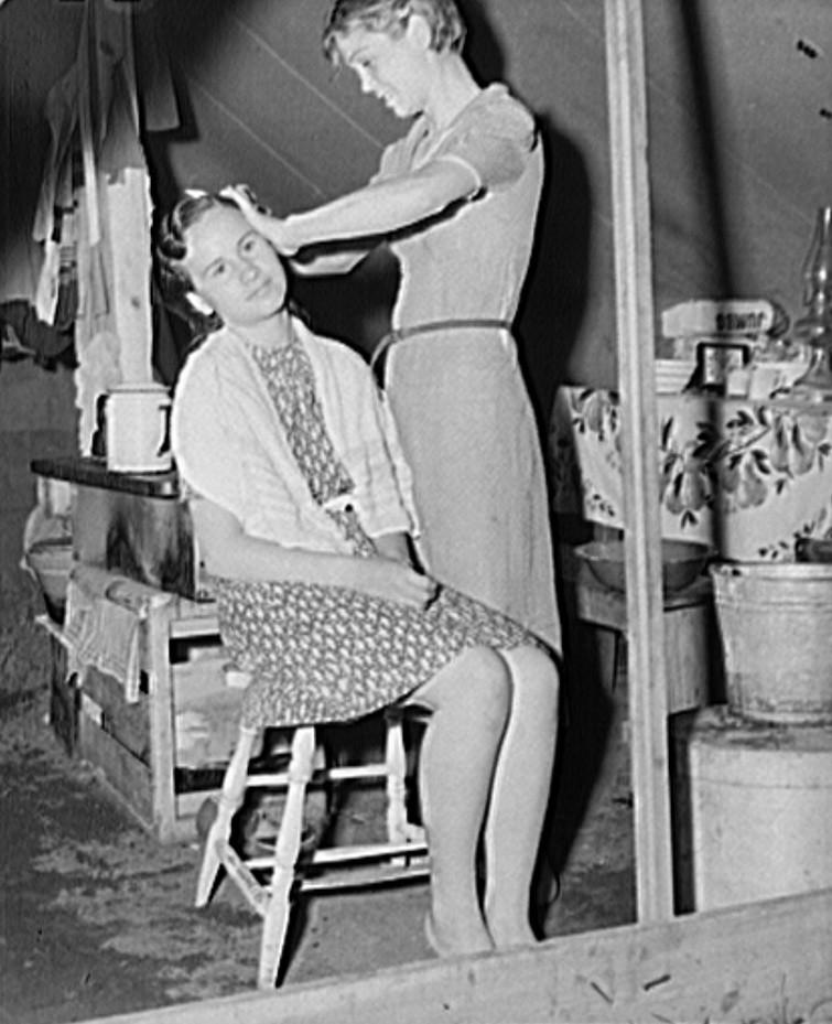 Migrant girl fixing her sister's hair. Roadside camp of fruit worker. Berrien County, Michigan 1940