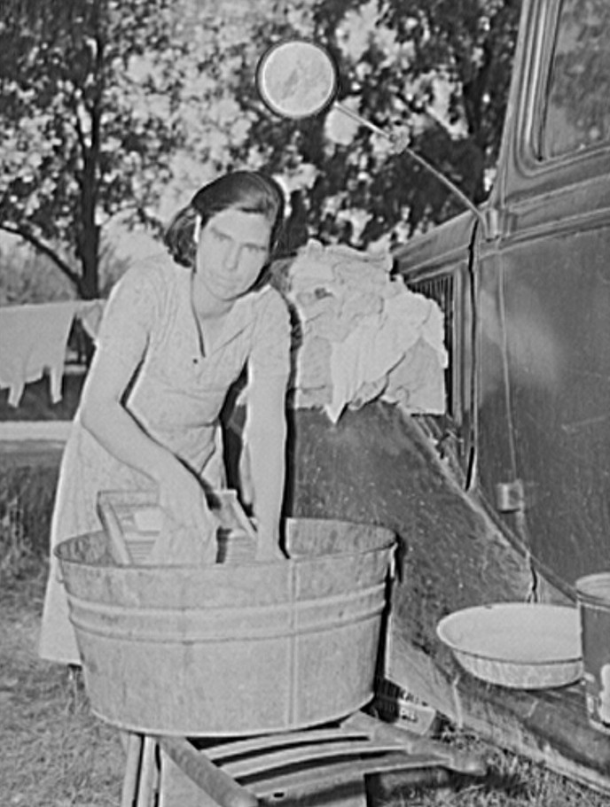 Mother of migrant fruit picking family doing family wash in roadside camp where fifteen farmers are living. Berrien County, Michigan 1940