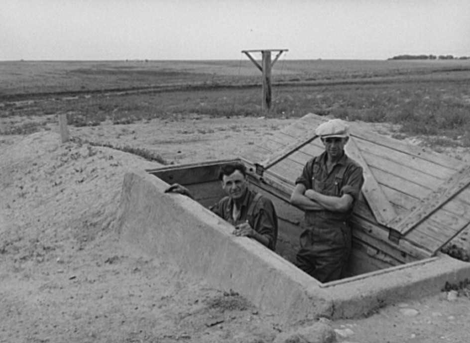 Mr. Shoenfeldt and son, FSA (Farm Security Administration) client in Sheridan County, Kansas, at entrance to fruit cellar which they built for six dollars and twenty cents