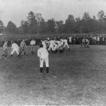Photograph shows a college football game with Joseph Maddock of the University of Michigan carries the football through a line of defenders; spectators in the stands. 1903