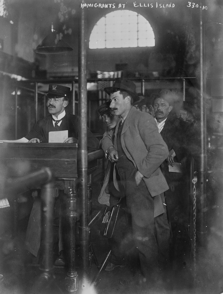 Photograph shows a man waiting, with others in queue behind him, at the registration desk in the immigration station on Ellis Island; an immigration official is seated at the desk. ca. 1908