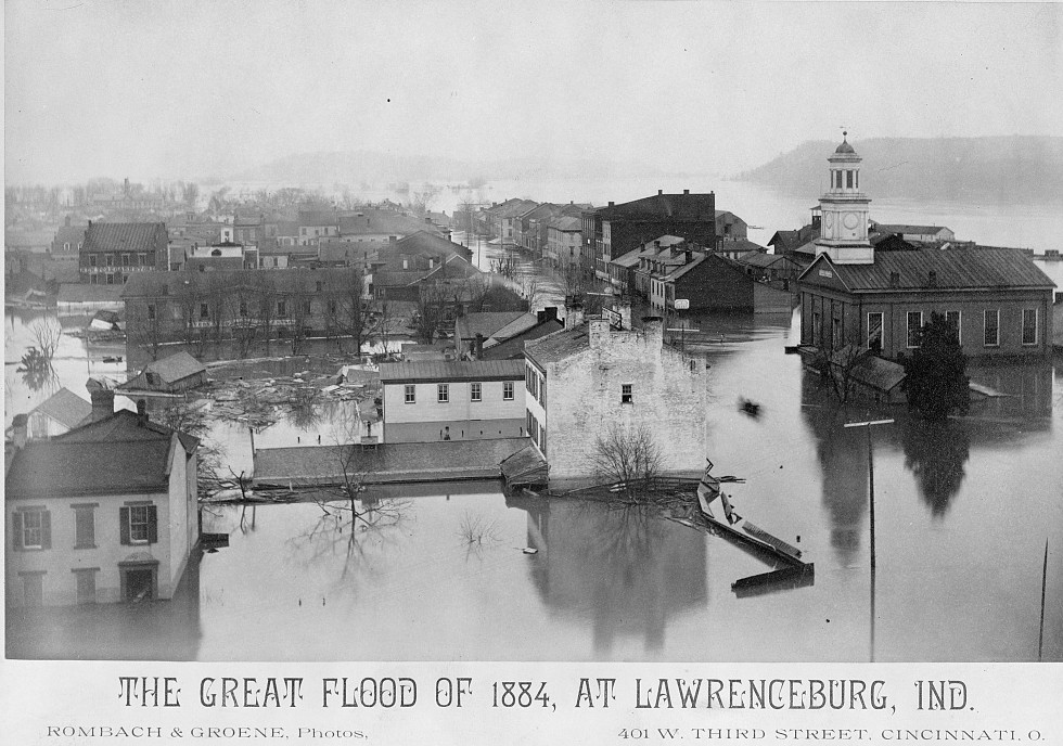 Photograph shows flood waters around city buildings in Lawrenceburg, Indiana, with city hall, topped with cupola or bell tower, on the right. may 4, 1884