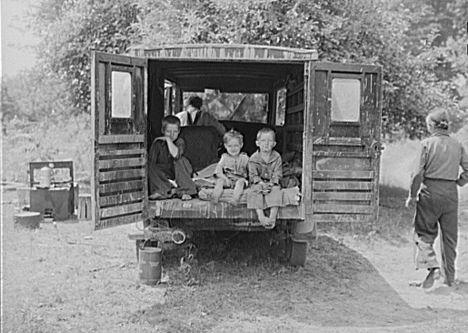 Rear of truck occupied by three children of migrant family from Arkansas. The parents sleep in a small tent. Berrien County, Michigan 1940