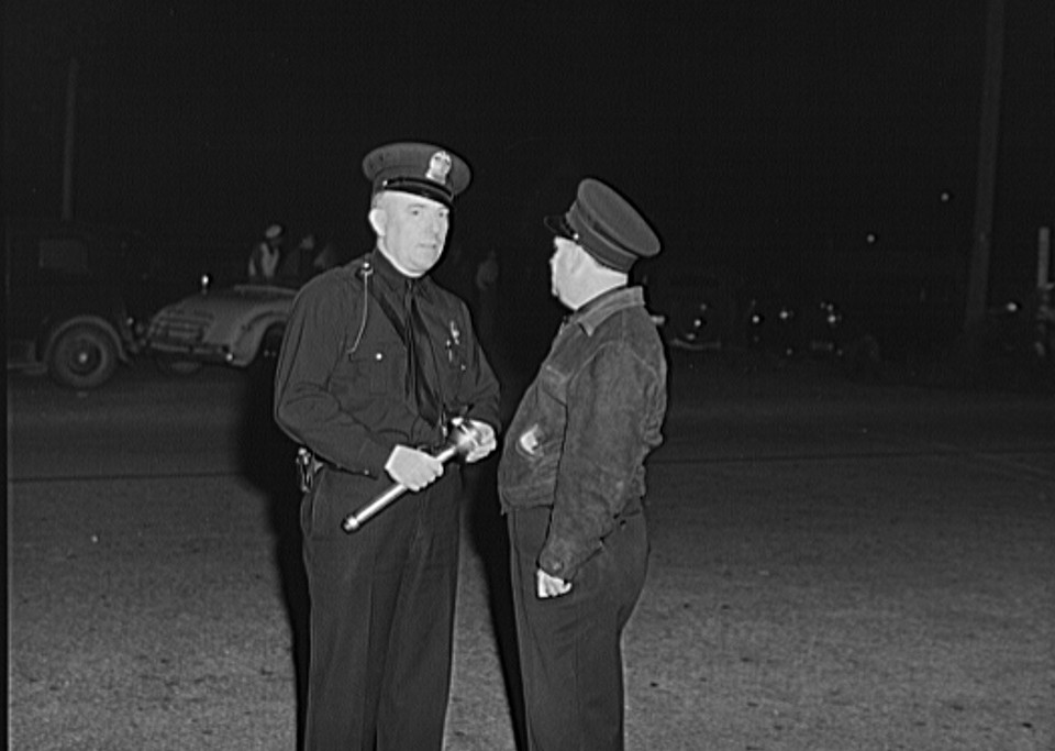Two policemen on the main street Saturday night when all the migrants come to town. Millburg, Michigan 1940