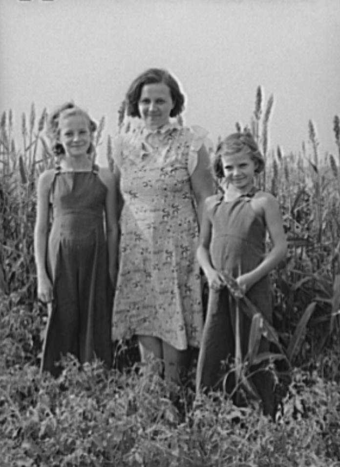 Wife of FSA (Farm Security Administration) client with her two daughters in garden. Kaffir corn in background is used as windbreak. Sheridan County, Kansas russell lee 1939