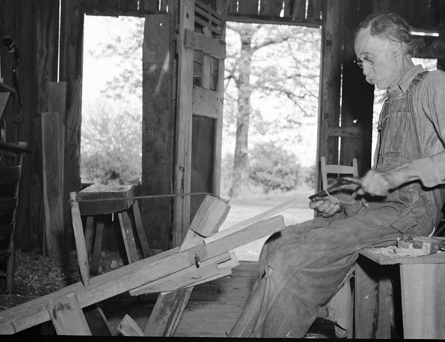 William Stamper, age eighty two, shaving oak sticks for chair braces in his workshop. Lake of the Ozarks passover area, Missouri by Carl Mydans May 1936
